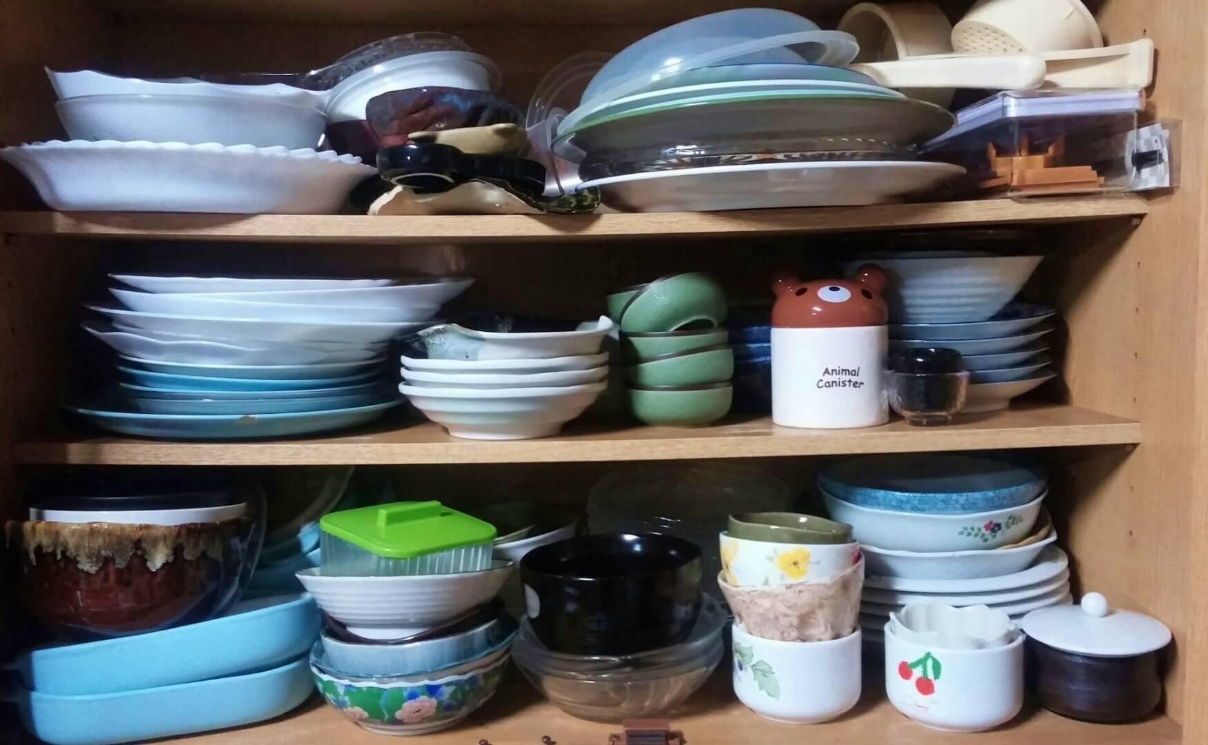 食器棚に詰め込まれた食器の画像