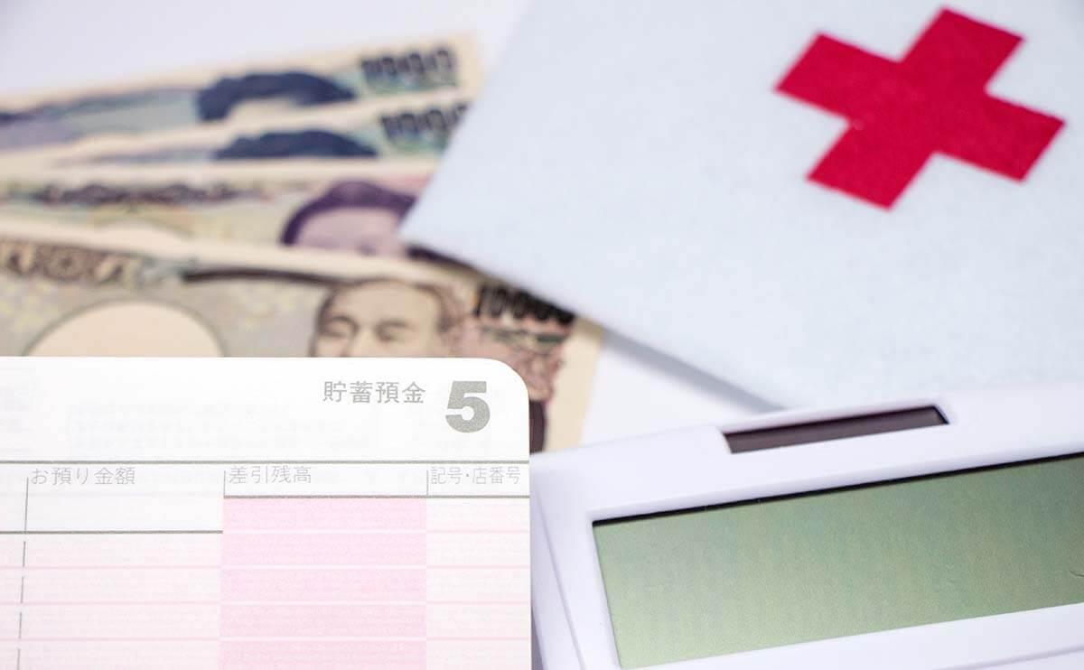 お金と通帳と赤十字の画像
