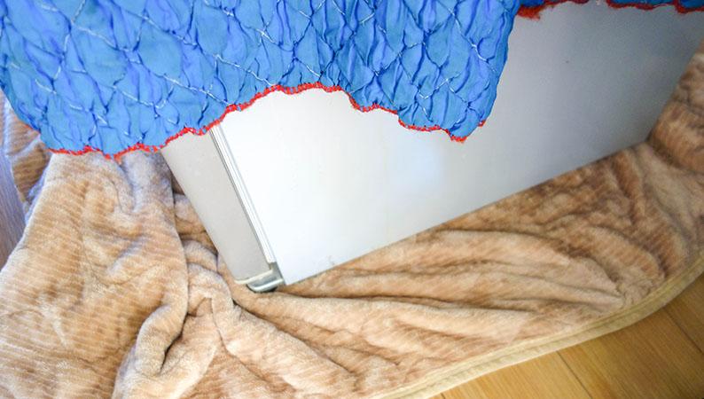 冷蔵庫の下に毛布が入れられた写真